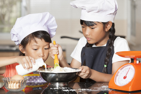 viscosity: Little asian girls pour milk to mix with wheat flour and egg Stock Photo