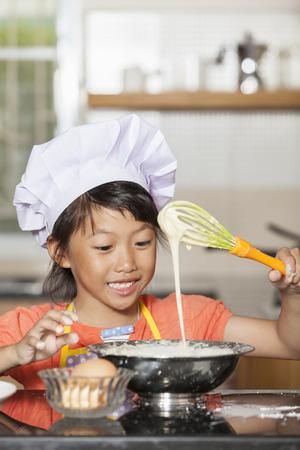 stiring: Little asian girls stiring wheat flour and egg