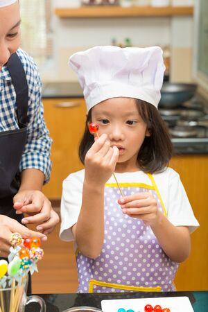 children learning: Mother and daughter making jelly candy in the kitchen in the kitchen