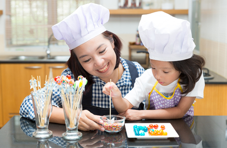 children learning: Mother and daughter making jelly ball in the kitchen Stock Photo