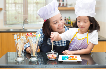 asian mother and daughter: Mother and daughter making jelly ball in the kitchen Stock Photo