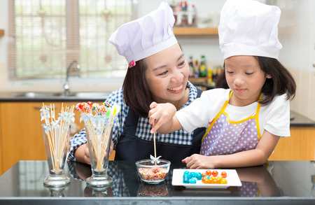 kids party: Mother and daughter making jelly ball in the kitchen Stock Photo