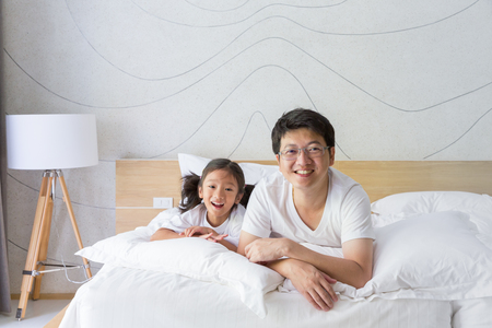 home life: Happy asian family father and daughter relaxing and smiling on white bed