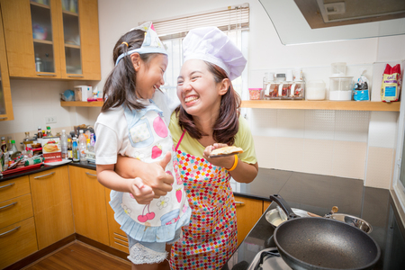 Asian family enjoy making pancake, Asian mother and daughter enjoy making bakery cake, Little Asian girl and mom enjoy decorate cake in real life kitchen,Asian mom teaching daughter to learn making pancake in real life kitchen at home Standard-Bild