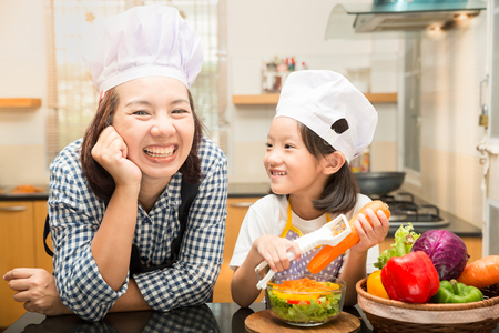 Asian mother teaching daughter making salad in kitchen,Cooking  concept of happy asian little girl and mother making salad for dinner and chopping paprika on cutting board with knife in kitchen Stock Photo