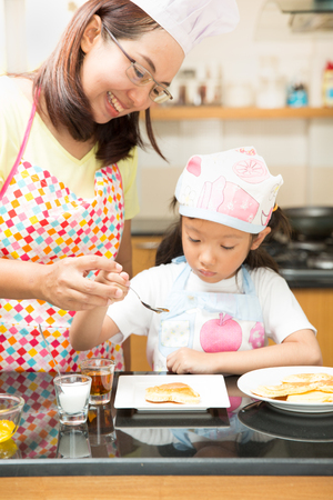 Asian family enjoy making pancake, Asian mother and daughter enjoy making bakery cake, Little Asian girl and mom enjoy decorate cake in real life kitchen,Asian mom teaching daughter to learn making pancake in real life kitchen at home Stock Photo