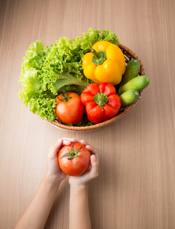 hand bell: Tomato on hand with fresh vegetable prepared in bowl on wooden table,Kid holding tomato with vegetable ingredient  in bowl on wooden table  preparing for making salad.