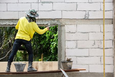 brick mason: Mason using trowel plastering the concrete to build wall, Construction under  building with mason plastering concrete to brick brick wall