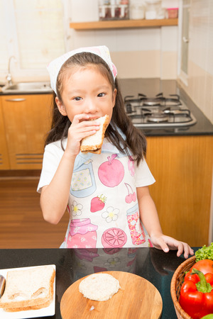 sanwich: Little asian girl learn to making tuna sandwich and eating the sandwich in kitchen, Concept of healthy food