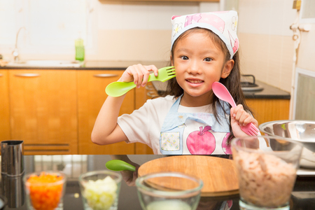 sanwich: Little asian girl holding spoon and folk enjoy making tuna sandwich in kitchen, Concept of kid learning to make healthy food, Tuna sandwich ingredients preparation ,
