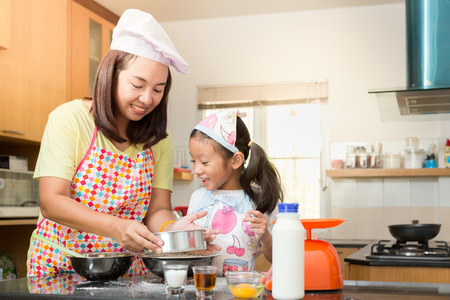 Asian family enjoy making pancake, Asian mother and daughter enjoy making bakery cake, Little Asian girl and mom enjoy decorate cake in real life kitchen,Asian mom teaching daughter to learn making pancake in real life kitchen at home 스톡 콘텐츠