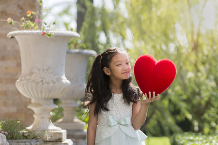 Little girl in white dress smiling and holding red heart pillow in garden, Valentine kid with heart in garden Stock Photo