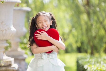 Little girl in white dress smiling and hug red heart pillow in garden, Valentine kid with heart in garden concept for valentine day