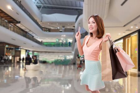 Asian girl enjoy holding credit card and paper bag in holiday with shopping mall blurred background,Concept of fashionist