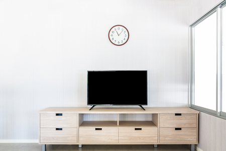 TV on wooden cabinet with clock on white wall Foto de archivo