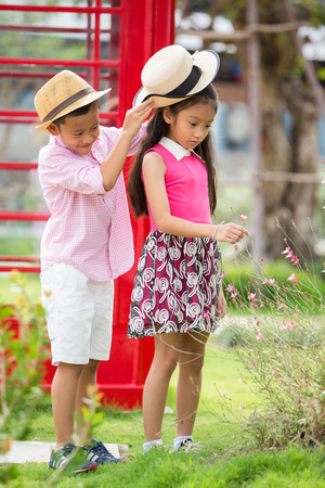 Little asian boy and girl enjoy playing on red sofa, Valentine or love concept