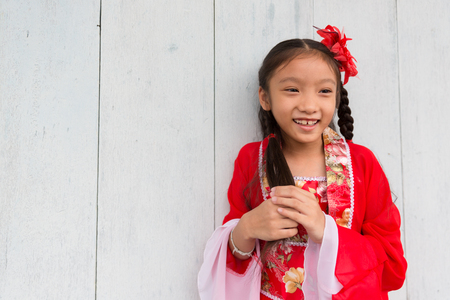 Young chinese girl in red dress posing for Lunar new year celebration