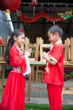 Young chinese boy and girl smiling and happy in lunar new year costume dress