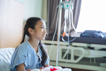 Child patient with saline solution on hand in hospital Stock Photo