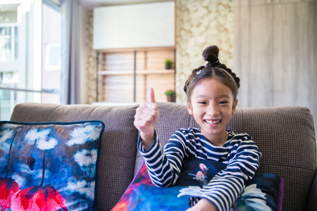 Little asian girl smiling and lift hand with thumb finger up in living room