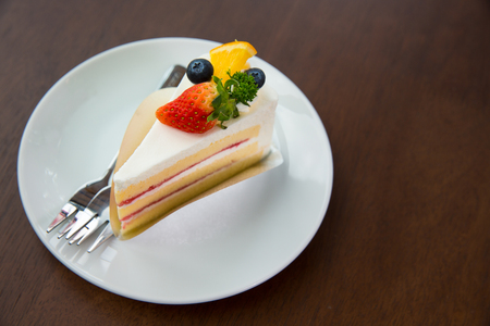 Fruit cake with whip cream topping strawberry and blueberry and orange on wooden table