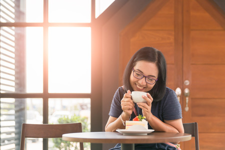 Tourist woman enjoy  drink coffee and eating fruit cake with whip cream topping strawberry and blueberry and orange on wooden table