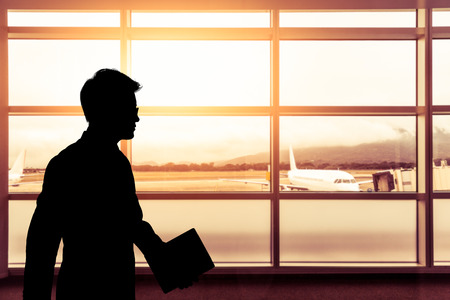 Silhouette businessman walking in airport with flare sunlight and airplane background,Business travel concept with toned color photo