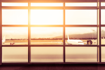 Airport window side at departure with flare sunlight and airplane background,Toned color photo Stock Photo