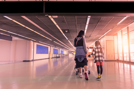 Family traveller walking with laggage cart in airport arrival or departure terminal with copy space black overhead board, Toned photo
