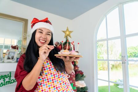 Cheerful asian woman happy eating chocolate cake for Christmas celebration at home