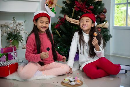 Little asian girl happy eating chocolate and dessert in Christmas celebration