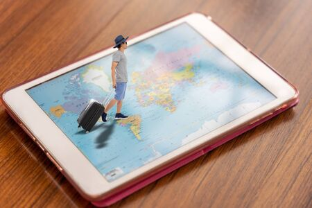 Tourist man in casual wear with luggage walking on world map in computer tablet, travel technology concept