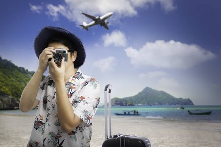 Tourist man in hat holding camera taking photo on sea beach background, Summer vacation travel trip concept