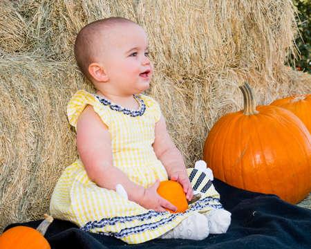 jovenes felices: Sonrisa del beb� en oto�o que se sienta por las calabazas y el heno