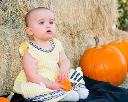 beautiful thanksgiving: Adorable Baby in Autumn sitting by pumpkins and hay Stock Photo