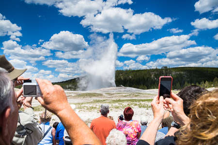 faithful: Tourists around Old Faithful geyser in Yellowstone National Park, USA