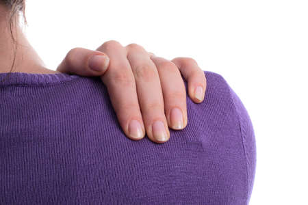 cramped: Pain In The Shoulder - A young woman holds her shoulder in pain! Isolated over white. Stock Photo