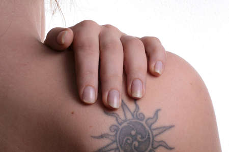 Neck Pain - A young woman holds her shoulder with tatoo in pain. Isolated over white. Stock Photo