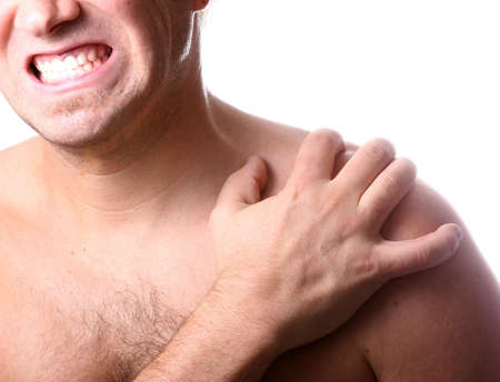 pectoral muscle: My Shoulder Hurts! A young man holds his shoulder in severe pain. Isolated over white!