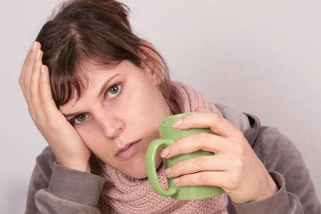hemorragia: Me siento enfermo - Esta joven mujer hermosa bebidas una taza de t�. su expresi�n facial muestra que ella se siente enferma.  Foto de archivo