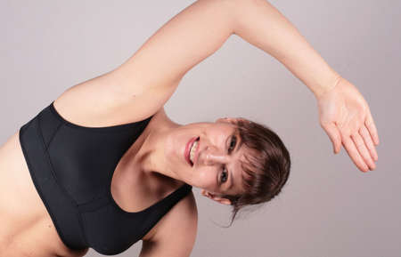 limber: Fit And Young - A young white woman is stretching after a work out.