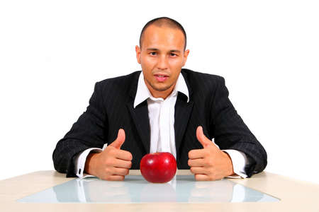 New Ways Of Business - Young businessman sitting in front of a red apple thinking with his thumbs up. Isolate over white. The table mirrors the image creating a nice effect! photo
