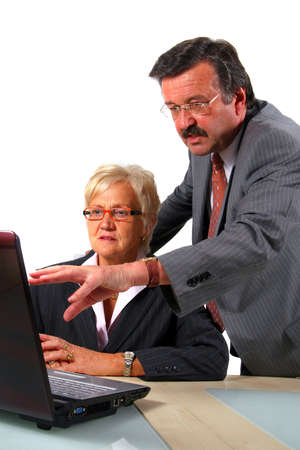 Senior Business People With Internet Business - A business woman and a man in front of a laptop on a desk. The man explains something to the woman. Isolated over white. Stock Photo - 3765868