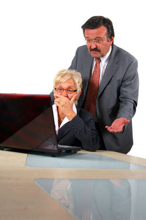 Senior Business People In Front Of Laptop - A business woman and a man in front of a laptop on a desk. The man explains something to the woman. The woman is shocked. Isolated over white. Stock Photo - 3765843