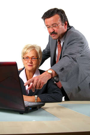 Senior Business Man Is Explaining - A business woman and a man in front of a laptop on a desk. The man explains something to the woman. Isolated over white. Stock Photo - 3784269