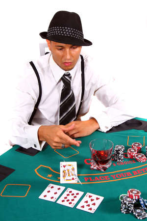 tokens: Young Poker Player Folding - Young poker player is tossing his cards with a hat and stylish suit. Isolated over white background. Stock Photo