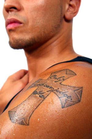 sexy tattoo: La cruz en mi brazo - Un joven hombre con un tatuaje de una cruz en su brazo. El texto en la cruz dice: S�lo Dios me puede juzgar. Aislado imagen m�s blanco.