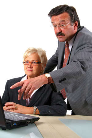 Boomers Working With Laptop - A business woman and a man in front of a laptop on a desk. The man explains something to the woman. Isolated over white.  Stock Photo - 3784322
