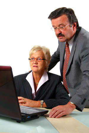 Senior Couple In Front Of Computer - A business woman and a man in front of a laptop on a desk. The man explains something to the woman. Isolated over white. Stock Photo - 3788412