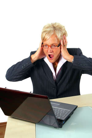 expressing: Shocked Businesswoman - A businesswoman in her fifties in front of a laptop shocked with her hands on her head. Isolated over white. Stock Photo